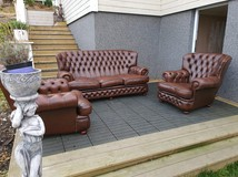 A pair of Chesterfield armchairs and a sofa