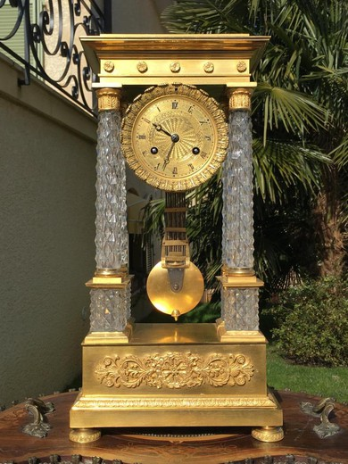 Antique clock in the style of Charles X. Made of gilded bronze and glass. France, XIX century.