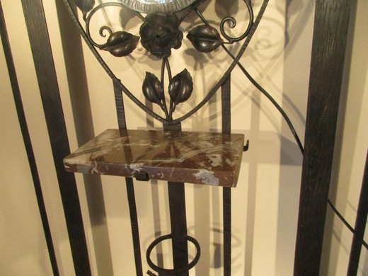 Antique coat rack with a mirror in the art deco style. It is made of metal. France, the 20th century.
